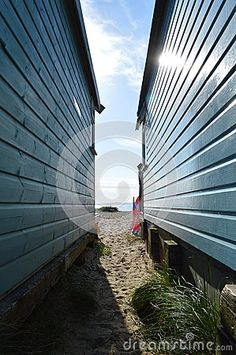 View between British beach huts through to sea and horizon. Sun shining, blue sky and view of Isle of Wight and groin.