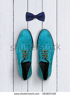 male shoes and bow-tie on a white wooden background