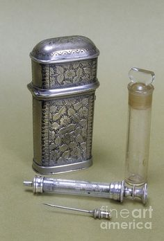 Silver plated etui (ornamental case) containing hypodermic syringe and bottle. This etui, engraved with a floral pattern is English and dates from around 1880.