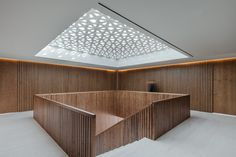Designed by Promontorio, the new Embassy of Egypt in Lisbon features robust concrete walls covered with bas-relief patterns that are inspired by traditional Egyptian motifs. - , Egypt Inspired Buildings, Embassy Architecture, Embassy Of Egypt In Lisbon Interior Stairs, Office Interior Design, Interior Design Services, Office Interiors, Arch Interior, Precast Concrete Panels, Concrete Wood, Wood Railing, Wood Architecture