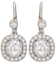 """Diamond drop earrings, suspending two old mine cut diamonds weighing approximately 2.15 total carats, with a pavé diamond surround and single circular-cut diamond surmount, on a platinum wire with gold security latch. Just under 1"""" total length with wire.   Via 1stdibs."""