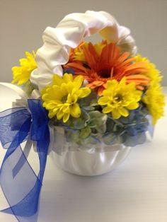 Flower Girl's basket of blue hydrangea, orange gerbera daisies, yellow daisies