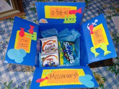 "New Missionary Package: ""It's o-fish-al, You're A Missionary."" Items inside: Goldfish Crackers, Tropical Skittles, Swedish Fish, Gummy Worms, & Gummy Sharks. Scripture put in card: ""Fishers of Men, Matt 4:19."