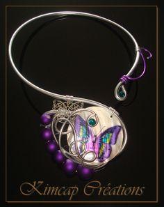 Collier fil aluminium argenté et lila. Palet de nacre (5cm), magnifique motif papillon aux couleurs irisées et scintillantes. Perles lila aspect gomme, filigrane papillon argenté. Double finition cristal Swarovski.