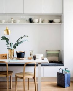 Built in banquette seating with storage and open shelf - great use of small space for sleek and scandi inspired dining room