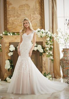 Vintage lace Appliqués on a soft net V-neck, fit n flare gown with a sheer back. Colors Available: White, Ivory, Ivory/Blush(shown).