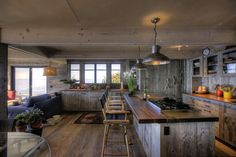 : Vintage Styled Rustic Cooking Room Arranged In Large Concept With Rustic Pendant Lighting Above Reclaimed Peninsula