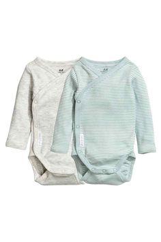 2 bodies de manga larga: CONSCIOUS. Bodies cruzados en punto de algodón orgánico suave con mangas largas y botones de presión en un lateral y en la entrepierna.