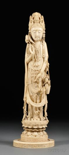 Tall Ivory Carving, China, 19th century, standing figure of Kuan Yin in an embellished robe, headdress decorated with a seated Buddha and two pheasants, with a windswept ribbon at the waist, hands holding flowers, standing on a lotus petal base, ht. 21 3/8 in.