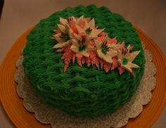 Basket-weave cake made for a customer's work party. The flavor is pineapple with a crushed pineapple filling. The frosting is key lime butter cream and the flowers are made from royal icing. Everything displayed is edible.