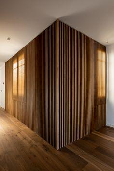 Estas lema de madera decoran la pared de este pasillo que vemos al entrar a la casa.  decoración - interiorismo - decor - minimal - minimalismo - nórdico - madera