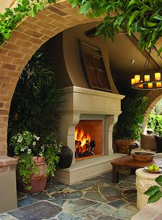 Arched entry into covered patio ~ love the fireplace!
