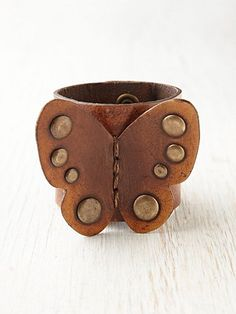 Distressed leather cuff bracelet with oversized leather butterfly attachment on front with stud detailing. Double snap button closure. Brand logo engraved on outside of cuff.
