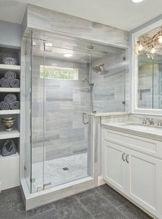 A mix of stone marble and tiles create a rich and elegant master bathroom. The shower is Lena white marble with a floor of small circular tiles the vanity a quartzite material and the floors a darker-toned limestone.