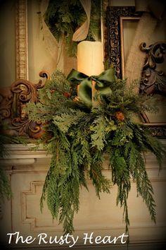Christmas candle dressed with evergreens and green satin ribbon
