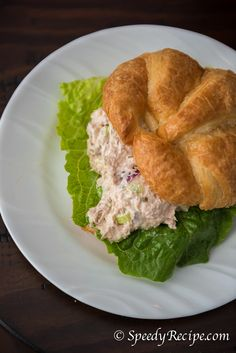 A simple tuna salad sandwich made from canned tuna, celery, red onion, scallions and mayonnaise with lettuce in between a Croissant bread.
