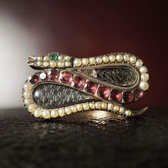 A Georgian ruby, emerald, pearl, and gold ring. The snake loops around two glass compartments, containing panels of woven hair.