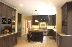 Platinum Kitchens: Dark cabinets with large hood and wood top.  bar area...
