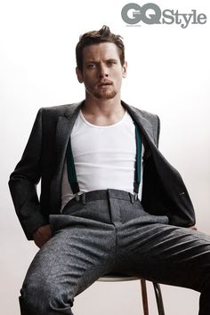 Jack O' Connell wears a white vest by American Apparel; grey wool blend slim-fit trousers by Givenchy by Riccardo Tisci; braces stylist's own
