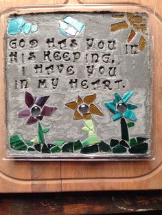 Starting to dry!!! Making a stepping stone DIY cement mix and glass pieces laid out. Each gem is a letter in a word, used to help me get a visual of spacing.. Flower stepping stone with sun, clouds and quote. God has you in his keeping, I have you in my heart. So adorable for my boyfriends pap for his grandmas grave that he ever so beautifully decorates, I hope this turns out nice!!! Easy so far...