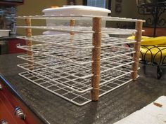 Homemade drying rack for kids artwork. I had leftover wire racks from some cube shelves and I used wine corks between them to make space. Just cut a little groove to sit the rack into it and used a glue gun to attach everything.