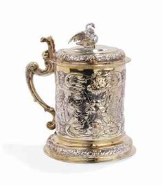 A German parcel-gilt silver tankard  Mark of Michael Jaske, Danzig, 1663-1678  Cylindrical, the circular foot chased with a band of flowers and foliage, the body chased with three cartouches, each enclosing a standing putto, further chased with scrolls, flowers and foliage, with leaf-capped scroll handle, bifurcated thumbpiece and hinged domed cover with detachable swan finial, marked on foot and cover rim  23.5 cm. high  1308 gr.