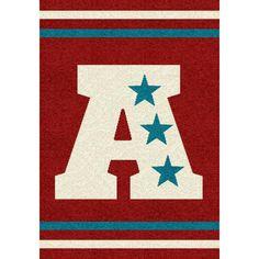 Tapis graphic NOBLESSE COSY avec un motif de style sport. Lettre A et étoiles. Dans les tons Rouge, bleu et beige.