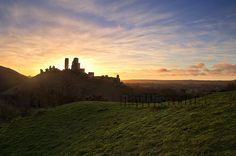 © All rights reserved.   Sunrise over Corfe Castle in Dorset. The castle itself is on the middle of three hills which distinctly shape the landscape... In the foreground mounds of green grass, in the background a sky of various colours breaks of the r . Beautiful !!!