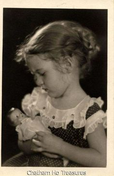 Little girl holding precious baby dol from an area that children 's clothes still looked like children not mini adults