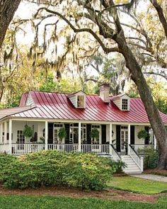 beautiful front porch with tall windows  and hanging ferns,    seamed, red tin roof