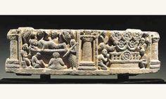Scène du mahaparinirvana  Schiste. 49 x 17 cm Art du Gandhâra. 3°-4° siècles  Rare relief au décor scandé de colonnettes, représentant à gauche l'épisode de la mort du Buddha, traditionnellement figuré couché sur la droite entouré de divers disciples et divinités. Sur la scène de droite montre le trône du buddha surmonté de cinq fleurs de lotus identiques à celle figurant en son centre, et symbolisant la roue de la loi bouddhique.