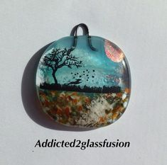 "Pet Ashes fused into glass sun catcher. This darling cremation sun catcher has your dog's ashes permanently fused between layers of glass in the walkway below the dog and tree image.  Hang it in your window or on a wall.  It measures approximately 2"" square, not including the hook at the top - by addicted2glassfusion"
