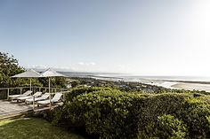 High on the mountainside overlooking Plettenberg Bay lagoon, Indigo House commands a spectacular view and boasts signature indigo, white and wood interiors. Rental Property, Pools, South Africa, Gazebo, Indigo, Outdoor Structures, Vacation, Beach, Garden