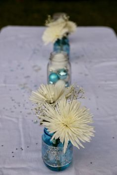 Frozen Birthday Party Ideas! I took blue mason jars and wrapped them in snowflake ribbon.  And then filled other clear mason jars with ornaments.  I literally re-used all my Christmas decorations for this party!