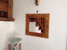 Specchio con cornice in materiale di recupero.