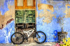 Land Town scape Photography of a modern bike parked outside a colourful old rustic house in the old of  Syros Island in Greece.