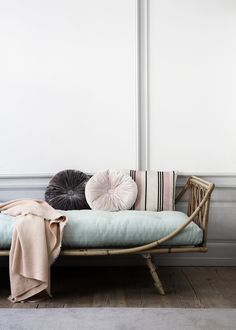 A rattan chaise with soft pastel pillows and throw