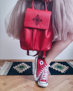 """The joy of wearing Iutta with this quirky outfit made up of a tulle skirt, red Converse shoes and the lovely red leather backpack Hawk with its black embroidery and traditional""""Bird in Space"""" motives. Red Converse Shoes, Backpack Outfit, Spring Wedding Colors, Designer Backpacks, Red Shorts, Black Women Hairstyles, Dusty Blue, Leather Backpack, Wear Red"""