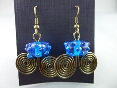 Blue lampwork beads added to a strand of spiraled bronze / copper wire and finished with plated surgical steel earwires. Wire Wrapped Earrings, Drop Earrings, Copper Wire, Lampwork Beads, Wire Wrapping, Plating, Bronze, Steel, Blue