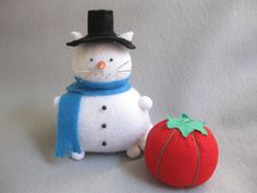 Snowman cat is a completely functional pincushion for sewers or can be used as a cool decorative piece. The majority of this pincushion was hand sewn. He, like all my other creations, is handcrafted and made from my own patterns.  This item consists of 1 cat pincushion and 17 assorted pins. The extra pins and tomato pincushion shown in certain pictures are not included. The cat pincushion is made of various colors of felt and materials.  This white kitty is ready for the snow to fall in his…