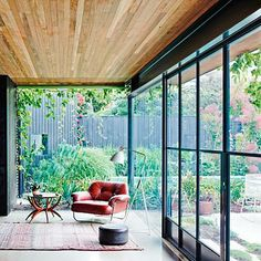 Open wall of glass leading to garden with wood ceiling