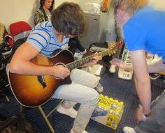 Louis plays guitar backstage in One Direction's dressing room at Jingle Bell Ball 2011