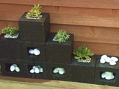 Planters Made from Cinderblocks : Home Improvement : DIY Network  Yard Crashers made one with full cinderblocks, painted colorful colors, some blocks turned out to create depth.  Glued something on bottom to hold dirt in