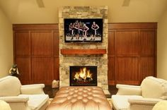 The best way to hide the entrance to a room is to keep people from suspecting it is there in the first place. This paneling on the whole wall on both sides of the fireplace looks like a normal wall treatment in an upscale home.