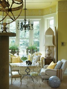 Sunny yellow walls are enhanced by stunning crown molding details and large windows that bathe the room in sunlight. Comfortable seating and a pair of houseplants make the room feel cozy as well as beautiful.
