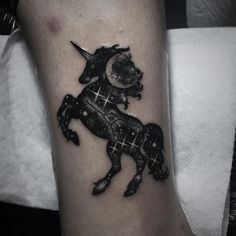 A mystical unicorn tattoo with the moon and stars drawn inside of it. The wonderful black silhouette theme of the unicorn is perfect in contrast with the night sky painted inside it.