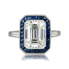 A deep blue cushion cut sapphire, adorned by a halo of sapphires and accented by a diamond studded fluer-de-lis. Sold by Estate Diamond Jewelry. Halo Diamond Engagement Ring, Vintage Engagement Rings, Emerald Cut Diamonds, Diamond Cuts, Beautiful Diamond Rings, Ring Displays, Diamond Jewelry, Gold Jewelry, Sapphire Jewelry