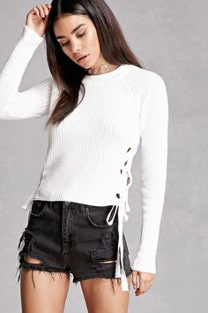 A midweight knit sweater featuring a cropped silhouette, lace-up sides with oversized grommets, a crew neck, and long sleeves. This is an independent brand and not a Forever 21 branded item.