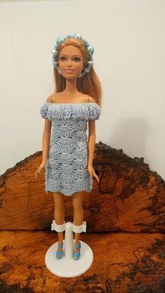 Barbie is wearing a light blue dress with a off the shoulder neckline. A beautiful bead headband is made with glass blue pearl. She has matching shoes to go a l