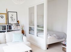 Sitting room / bedroom with widow divider in a charming, small swedish home in white and pastels
